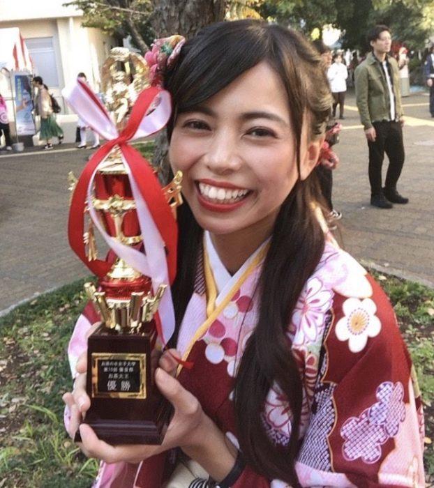 大学のクイズ大会で優勝!かっこいいトロフィーを手に喜んでいます。チーム対抗戦で、仲間とともに勝ち取りました!